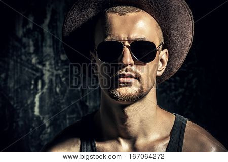 Portrait of a masculine brutal man in a hat and sunglasses over grunge background. Denim collection. Male fashion.