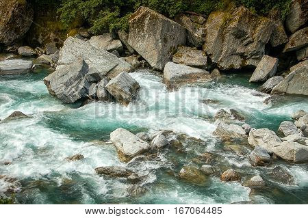 Strong current erodes the rocks in Thunder Creek on the South Island of New Zealand