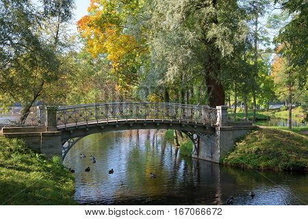 Openwork iron bridge over the canal the Sunny September day. The Gatchina Park