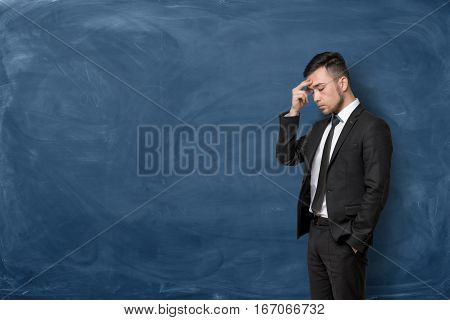 A businessman in a black suit standing with his hand on his forehead on blue chalkboard background. Business planning. Looking for opportunities. Management challenges.