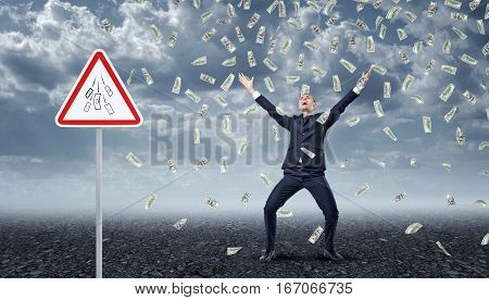 Ecstatic businessman standing under many dollar bills falling from the sky with a traffic warning sign 'Money' nearby. Business and money. Success and profit. Dollar bills.