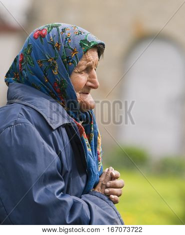 Bacau,Romania - April 20,2008:Portrait of an unidentified old poor woman praying outside in a church garden in Bacau,Romania on April 20,2008.