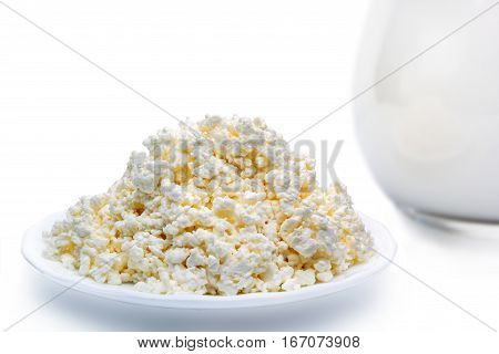 cottage cheese on a plate next to a jug with milk. isolated