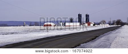 Rigaud, Quebec, March 5, 2016 -- A long road and snow covered landscape lead to a colorful farm with large silos in the distance. Shot near rural Rigaud, Quebec, on a slightly overcast but bright day in March.