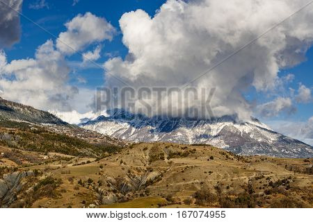 Mont Guillaume mountain covered in snow and clouds with Saint Apollinaire village on the right. Winter in the Southern French Alps. Hautes-Alpes France