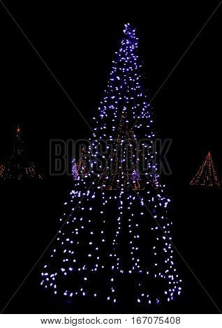 Vertical of whimsical artistic Christmas trees made up of strings of blue and red lights glowing brightly in a small park late at night in Niagara Falls, Ontario, on a dark late November evening. High exposure on light bulbs at 100%; suitable for web or p