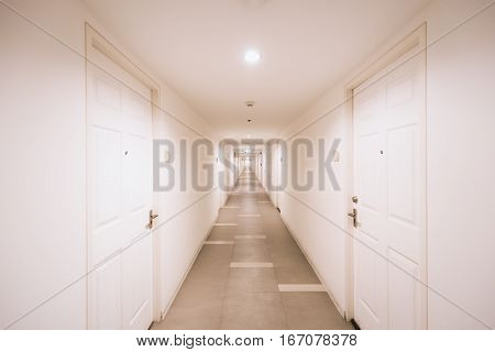 Corridor inside white building in orange tone lamp. Position of room doors are opposite alongside the way.