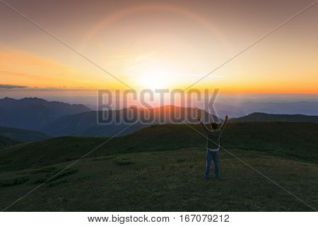 traveling man rising victory hand with succsessful and freedom feeling on high mountain against beautiful sun set sky