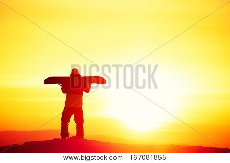 Snowboard and ski concept with snowboarder on mountain top at sunset time. Space for text