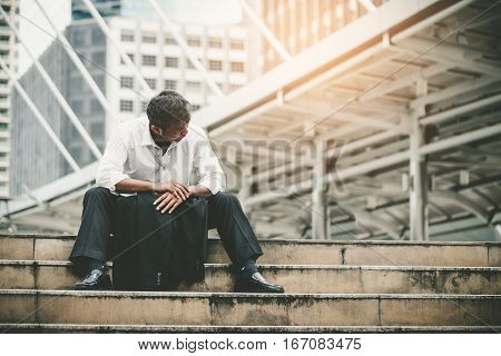 Tired Or Stressed Businessman Sitting On The Walkway In The City After His Work. Image Of Stressed B