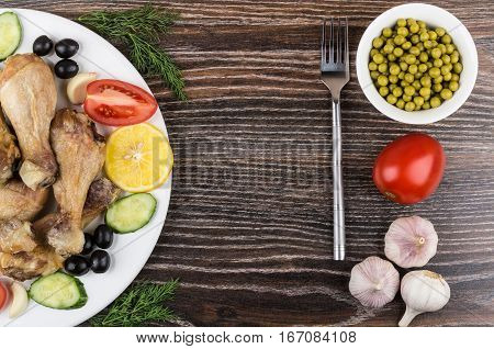 Fried Chicken Legs With Vegetable, Olives And Lemon On Table