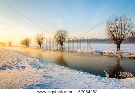 Winter landscape of a polder with a frozen stream in the Netherlands. It is early in the morning of a beautiful day the sun is rising and some morning mist is still visible above the field.