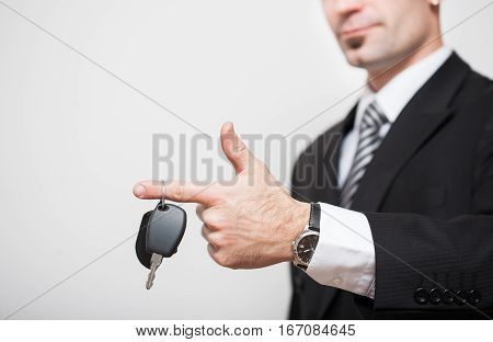 Man in business suit holding car keys in hands.