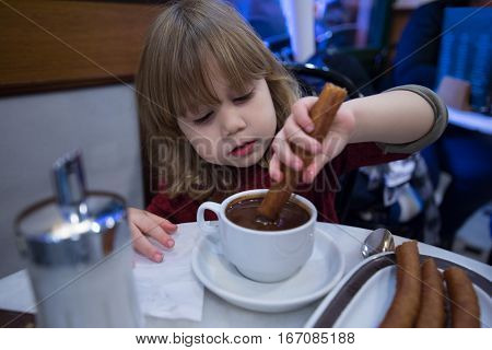 Child Dipping Churros In Chocolate