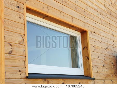 Close up on Plastic PVC Window in New Modern Passive Wooden House Facade Wall. PVC Windows are the Number One in Energy Efficiency.
