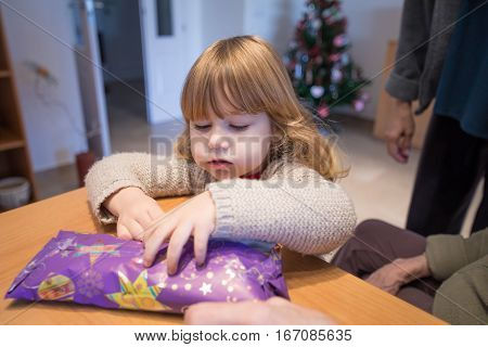 Child Looking To Open Christmas Present Wrapped In Paper