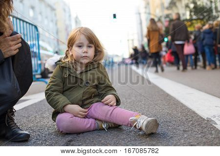 Crying Little Child Sitting On Asphalt Street