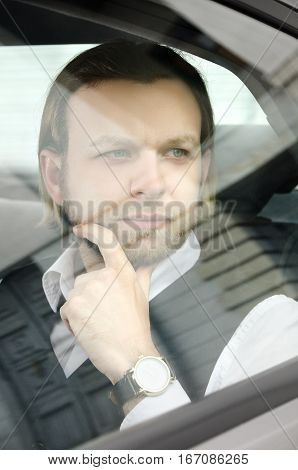 Young Businessman And Looking Away Thru The Glass While Sitting In Car.