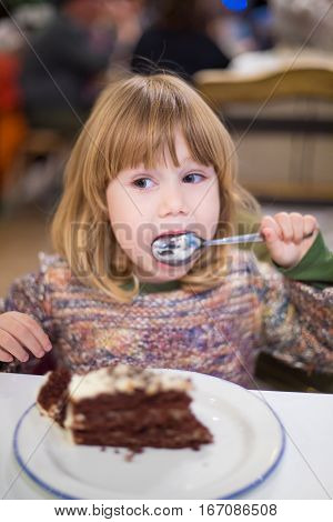 Little Child Licking Spoon With Chocolate Cake At Restaurant