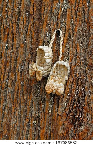 Small souvenir bast shoes hanging on a tree