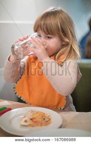 Little Kid Drinking Water Glass At Pizza Restaurant