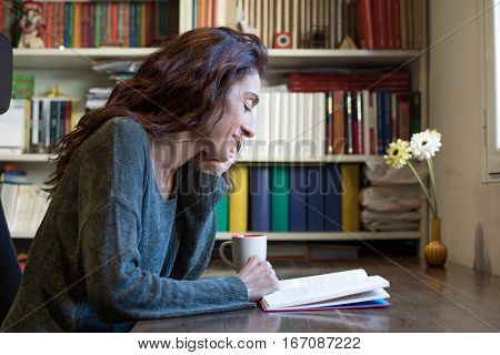 Smiling Woman Reading Book On Wooden Table