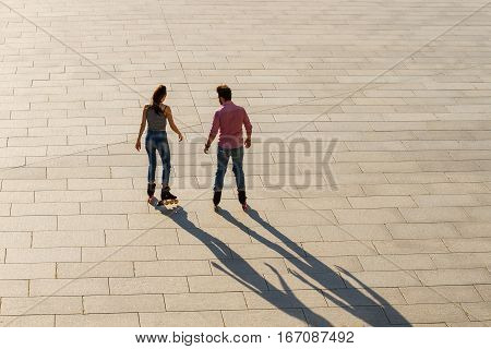 Back view of rollerblading couple. Man and woman outdoors. Our new active hobby.