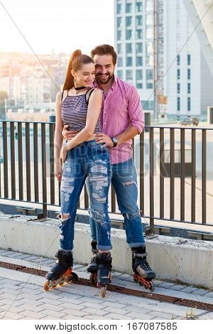 Smiling couple on rollerblades. People on urban background. We're young and free.