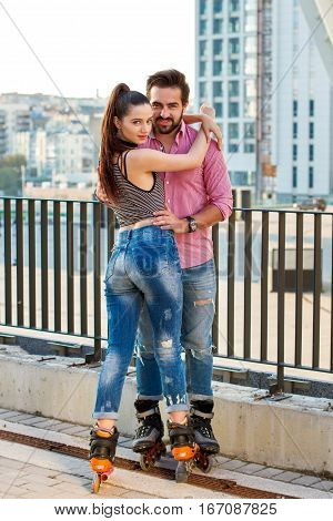 Woman and man on rollerblades. Couple standing on city background. Getting to know each other.