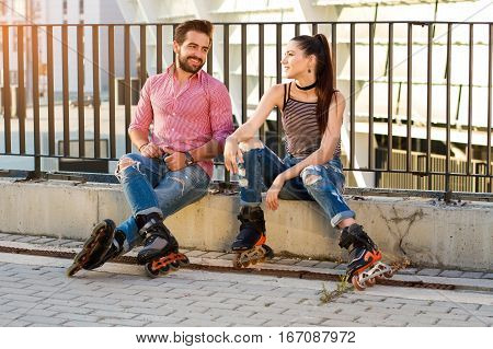 Couple on rollerblades sitting. Guy smiling to a girl. Original idea for first date.