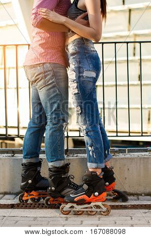 Couple's legs on rollerblades. Man and woman wearing jeans. Sport and fashion.