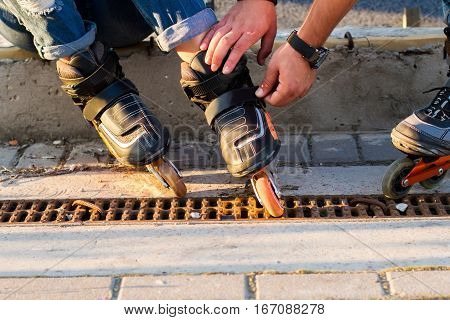 Male hands touching rollerblades. Black inline skates. New sports equipment.
