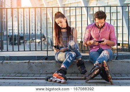 Couple with phones sitting. Inline skaters on urban background. Pay attention to your partner.