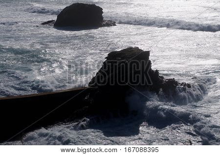 Waves of rising tide near a fishing port in southern Portugal