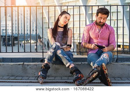 Couple with phones is sitting. Bored woman looking at man. Who are you texting.