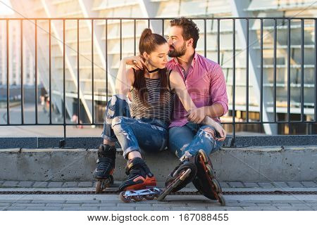 Couple on rollerblades sitting. Two people in the street. Time spent together is priceless.