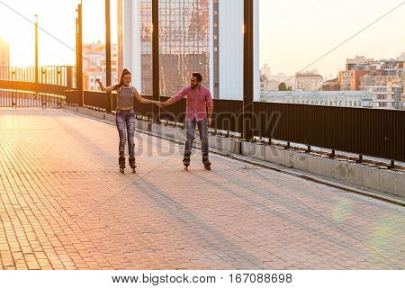 Couple holding hands and rollerblading. People on sunrise city background. Our road to happiness.