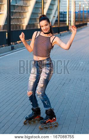 Woman smiling and rollerblading. Cheerful girl on urban background. Watch me roll.