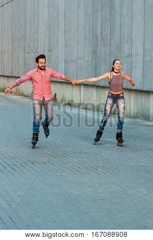 Man and woman rollerblading. Couple smiling and holding hands. Good impressions and cheerful mood.