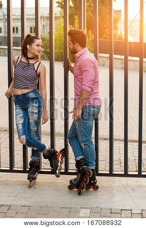 Couple on inline skates standing. Young woman looking at man. Date of active people.