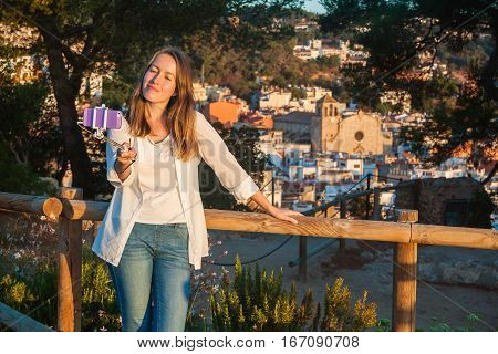 Young girl taking a selfie with a stick. Tossa de Mar Catalonia Spain.