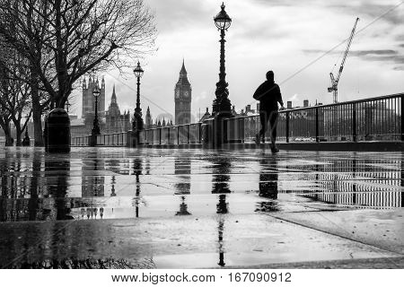 Silhouetted jogger runs along the Southbank on a rainy day in London