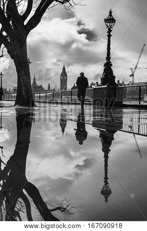 Man and Big Ben reflected in large puddle on the Southbank of the Thames