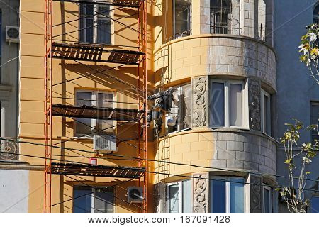 Volgograd Russia - November 06 2015: Builder worker painting facade of building house in Volgograd
