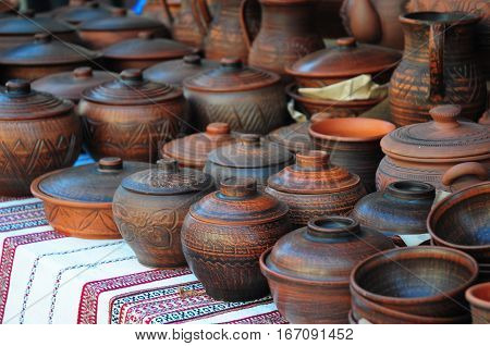 Traditional Ceramic Jugs on Decorative Towel. Showcase of Handmade Ukraine Ceramic Pottery in a Roadside Market with Ceramic Pots and Clay Plates Outdoors.