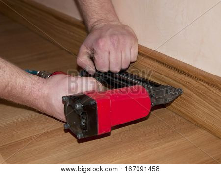 Repairman's hands Installing Skirting Board Oak Wooden Floor. Handyman repairing with hammering a nile into a skirting board.