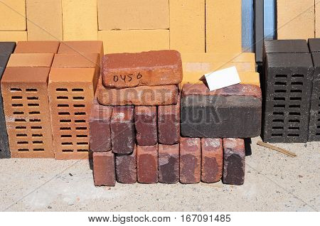 Colored building blocks bricks and concrete pavers (paving stone) or patio blocks organized on pallets for sale stored on metal shelves outdoors.