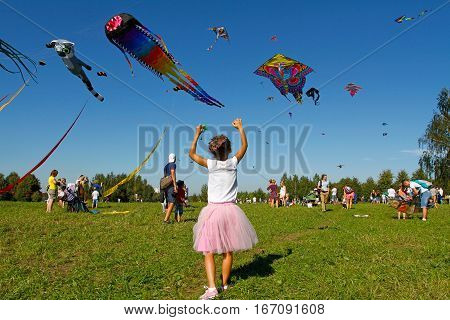 Moscow Russia - August 27 2016: Girl launches a kite into the sky at the kite festival in the Park Tsaritsyno in Moscow