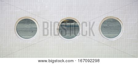 3 round mirror windows in a row on a white tiled building wall background