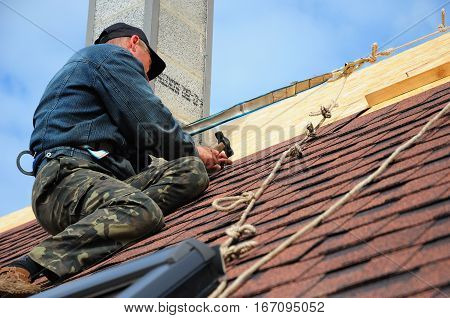 KYIV, UKRAINE - March 1, 2017:  Roofing Contractor. Roofing Construction and Building New House with Modular Chimney Skylights Attic Exterior. Roofers Install Repair Asphalt Shingles or Bitumen Tiles on the Rooftop Outdoor. Asphalt Shingles laying and ins